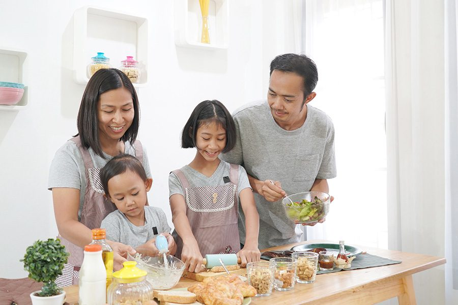 Personal Insurance - Happy Mother and Father Teach Their Two Children How to Cook in the Kitchen