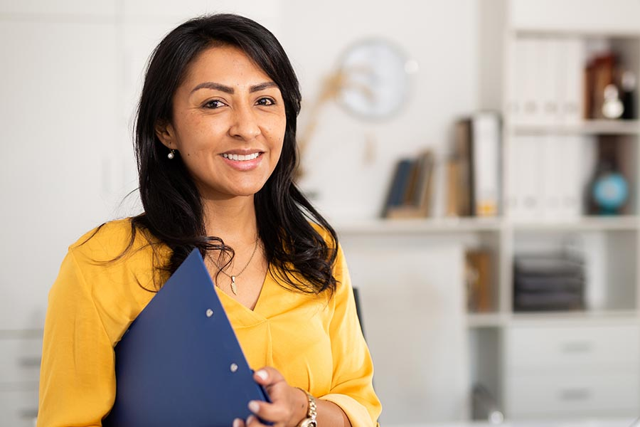 Business Insurance - Businesswoman in Yellow Blouse Holding a Clipboard in a White Modern Office