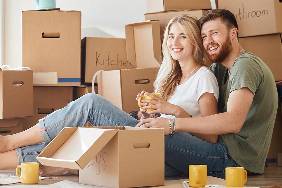 Real Estate - Young Couple Sitting Amongst Boxes in Their New Home Drinking Coffee