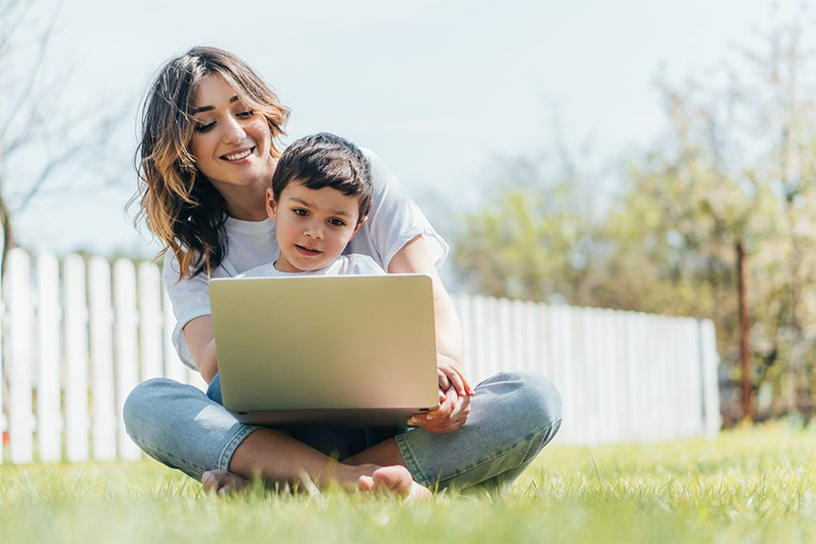 Client Center - Portrait of a Mother and Her Son Sitting in the Backyard on Green Grass While Using a Tablet on a Sunny Day