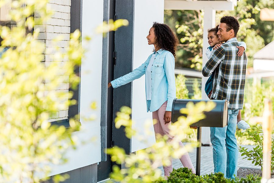 Personal Insurance - View of a Happy Family with a Young Daughter Getting Ready to Walk Through the Front Door of Their New Home