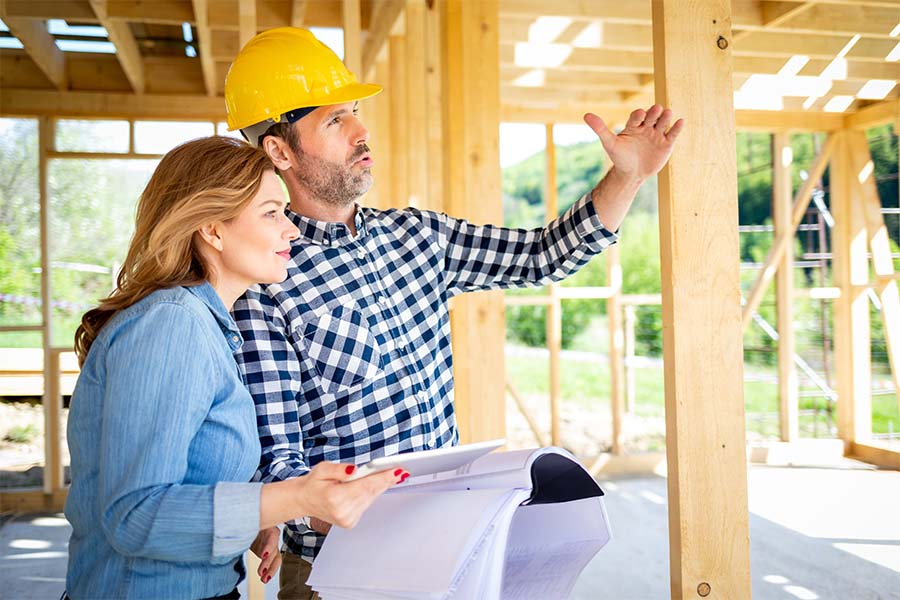 Specialized Business Insurance - Portrait of a Contractor Standing in a New Framed Home and Speaking to a Client About the Building Details