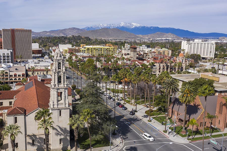About Our Agency - Riverside, California Seen From Above, A Street Lined With Palm Trees, Large Buildings, and Snow-Capped Mountains in the Distance