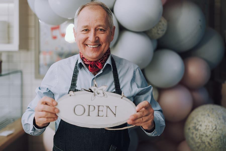 Business Insurance - Business Owner Wearing Overalls and a Red Bandana Holds an Open Sign, A Balloon Arch Behind Him