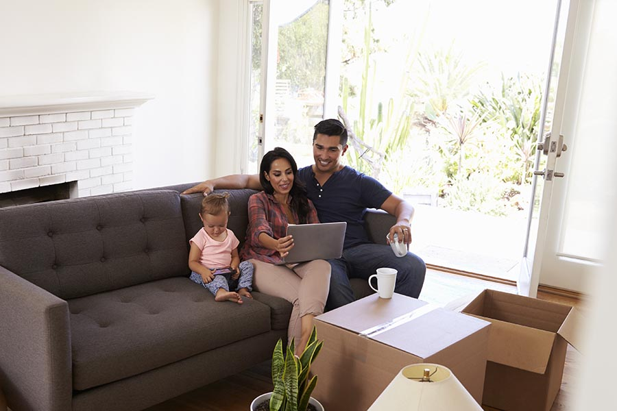 Client Center - A Couple and Their Young Daughter Use a Computer on a Gray Couch, Moving Boxes All Around Them