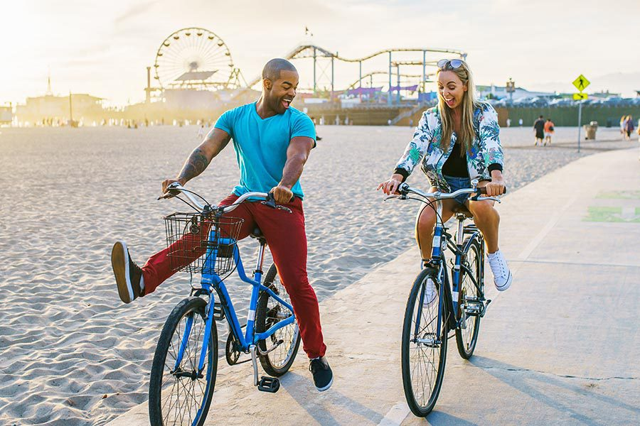 Personal Insurance - Happy Couple Laughing and Riding Bikes on a Beach Path, An Amusement Park Behind Them