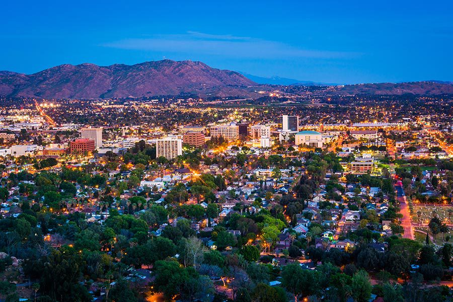 Riverside, CA Insurance - Riverside, California Seen From Above at Night, City Lit Up, Many Green Trees, and the Mountains Glowing Purple in the Distance