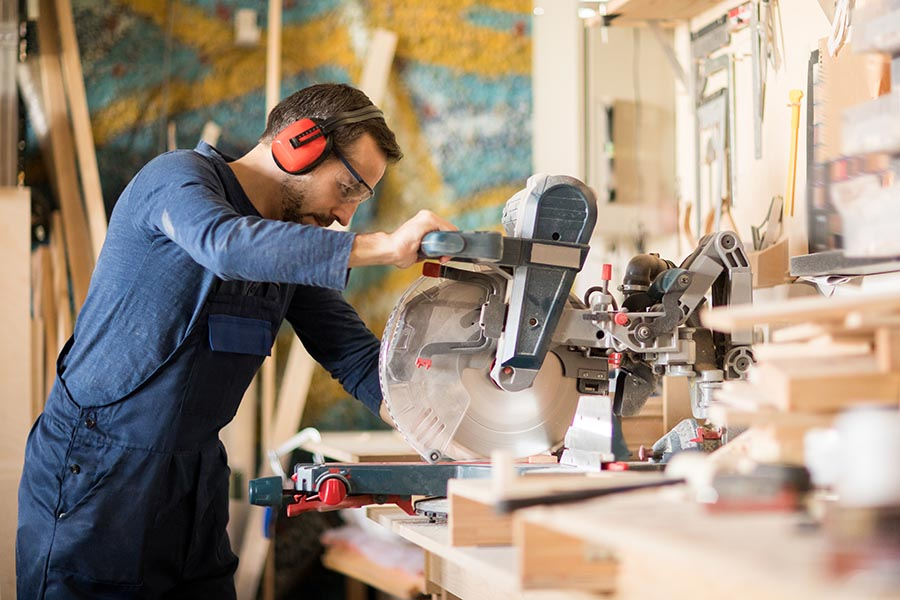 Specialized Business Insurance - Contractor Using a Circular Saw In His Wood Shop, Wearing Overalls and Protective Gear