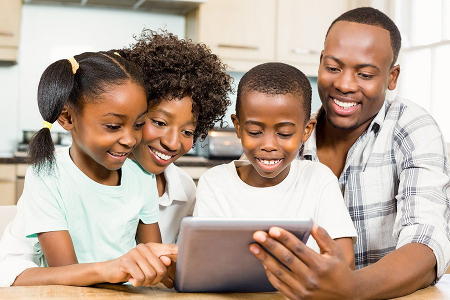 Client Center - Happy Family Using Tablet in Kitchen to Chat with Others