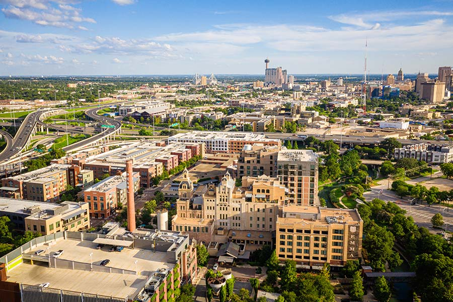 Contact - Aerial of Pearl District San Antonio Texas Displaying Multiple Buildings, a Bridge, and Trees on a Bright Day