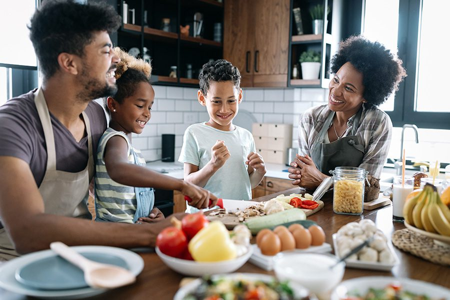 Personal Insurance - Happy Family in the Kitchen Having Fun and Cooking Together
