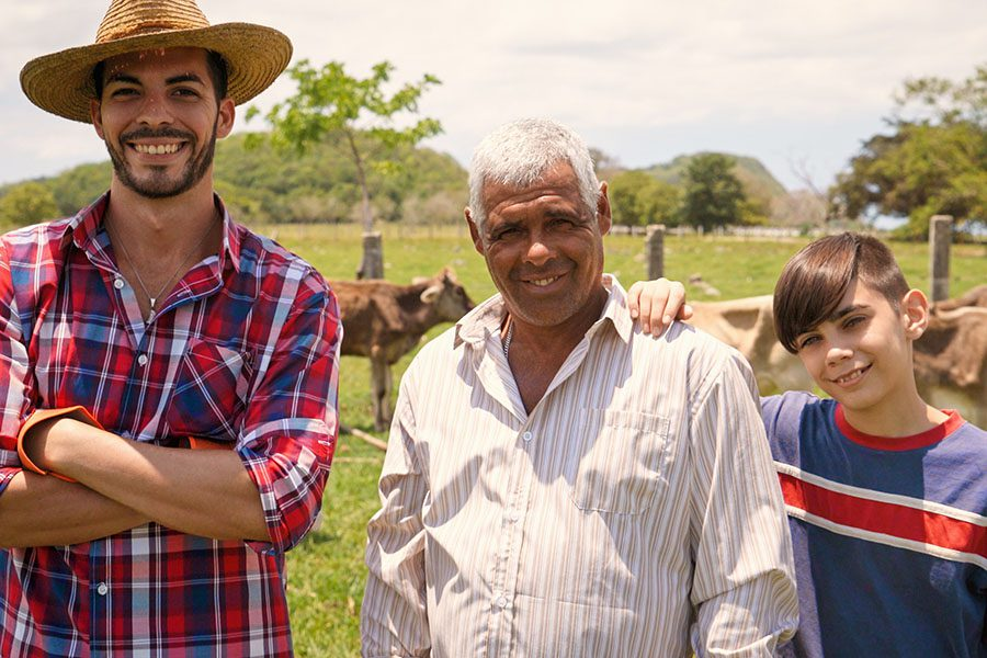About Our Agency - Three Generations Family Portrait Of Farmers In Farm on a Sunny Day