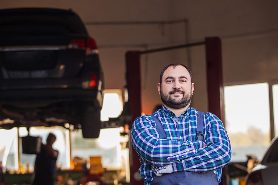 Business Insurance - A Skilled Auto Mechanic in Standing Front of His Own Workshop With His Arms Crossed