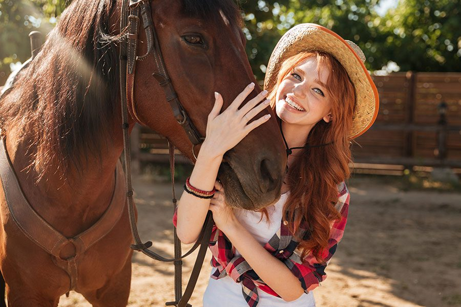Hospitality Insurance - Happy Woman Cowgirl in a Hat Standing and Hugging Her Brown Horse