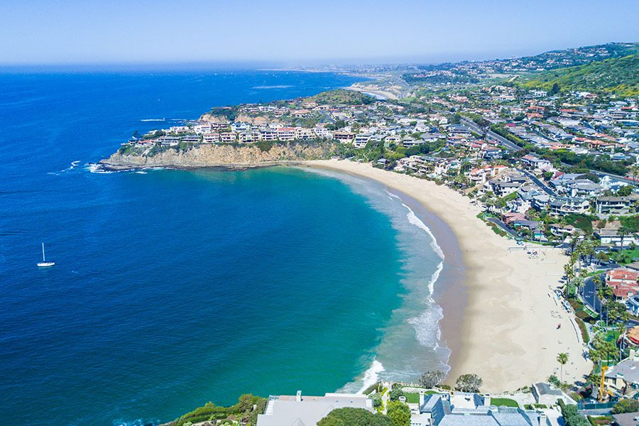 Contact - Aerial View of Emerald Bay, Laguna Beach, Southern California Displaying the Ocean With a Few Boats, the Beach, and City on a Sunny Day