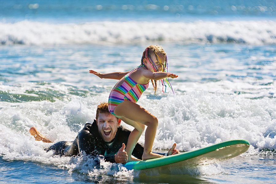 Personal Insurance - Little Surfer Girl Learning to Ride on a Surfboard With an Instructor Behind Her in the Ocean