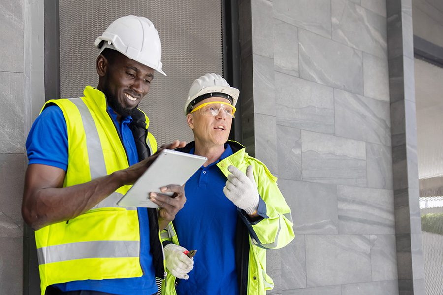 Specialized Business Insurance - Two Industry Engineers Use Digital Tablet to Discuss About Their Work at a Construction Site