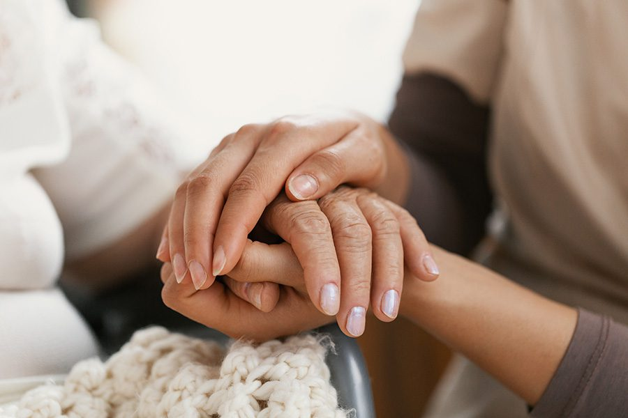 Final Expense Insurance - Closeup of a Woman Holding Hands with a Senior Patient