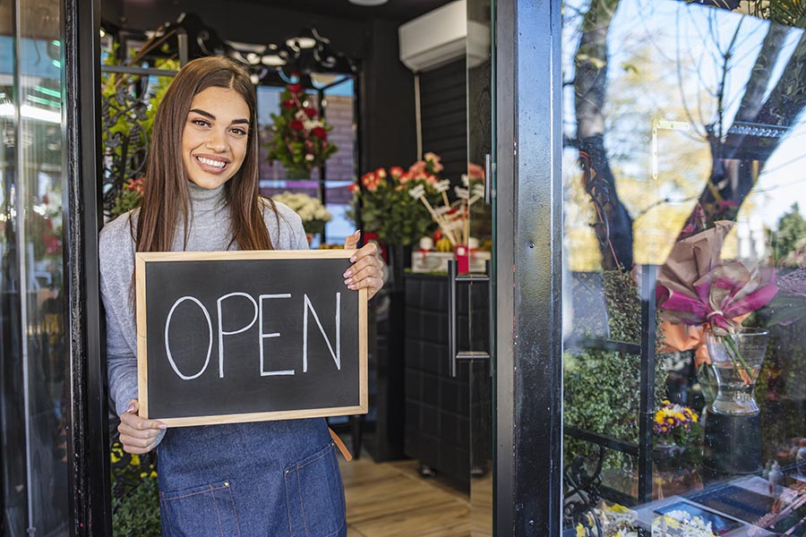 """Business Insurance - Young Business Owner Holding a Chalkboard Sign Reading """"Open"""" at the Door to Her Flower Shop"""