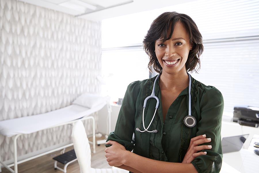 Life and Health Insurance - Doctor Wearing a Stethoscope in an Exam Room, Smiling