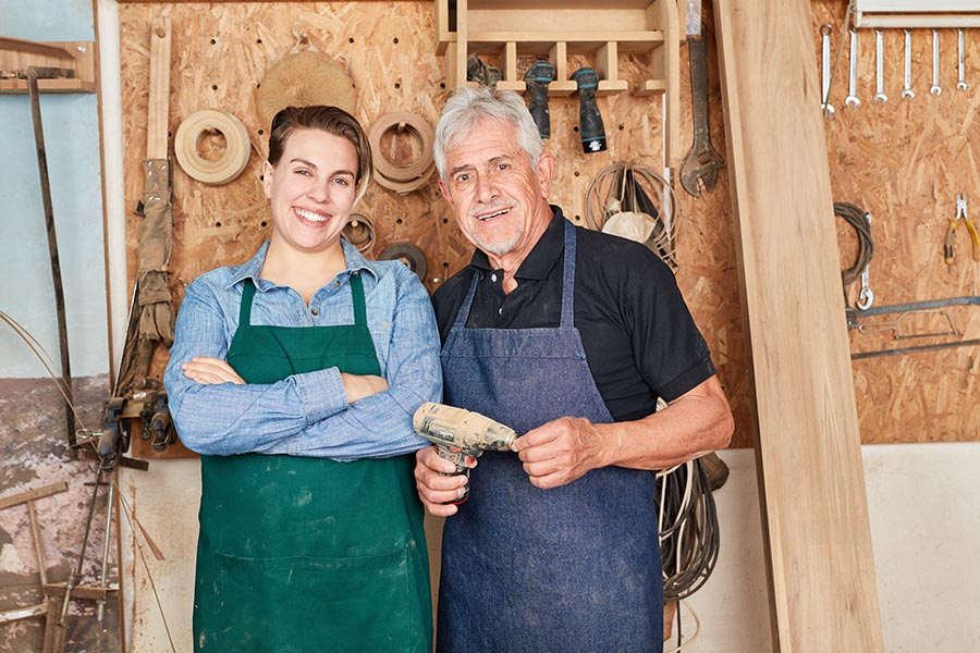 Specialized Business Insurance - Father and Daughter Contractors in a Wood Shop, Wearing Aprons and Standing in Front of Tools