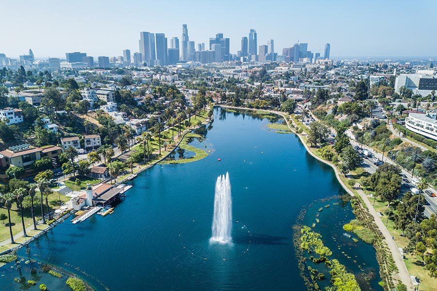 About Our Agency - Echo Park in California, Lake With Fountain in the Foreground, the Los Angeles Skyline in the Distance