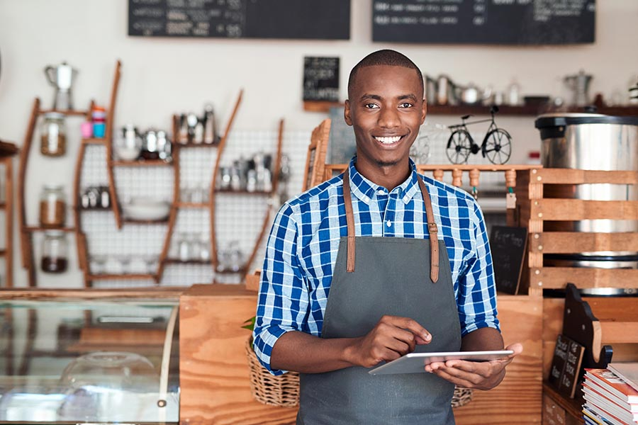 Business Insurance - Business Owner Uses a Tablet While Wearing a Denim Apron, Standing in Front of His Shop Counter