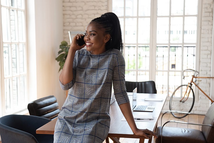 Client Center - Businesswoman Makes a Call, Leaning on a Conference Table