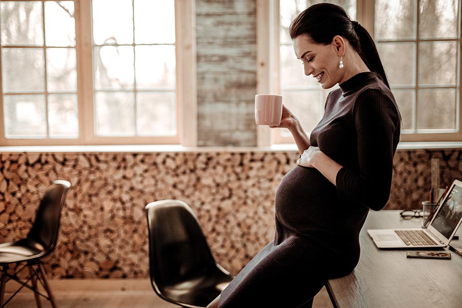 Employee Benefits - Pregnant Businesswoman Admires Her Baby Bump, Drinking Coffee in a Modern Office Space