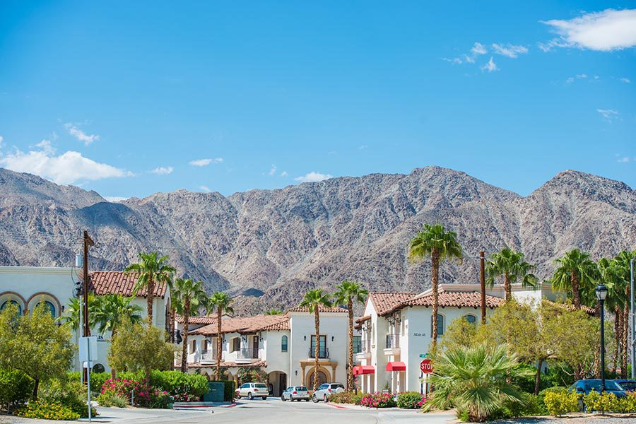 La Quinta, CA Insurance - Beautiful Buildings With Terra Cotta Tiled Roofs, White Walls, and Beautiful Landscaping, Surrounded by Palm Trees and Large Mountains