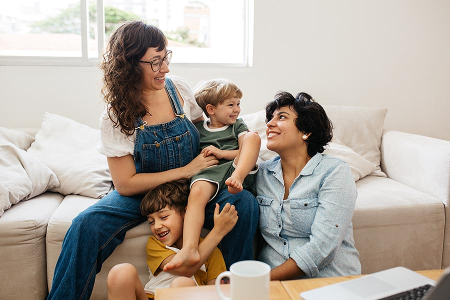 Personal Insurance - Family Cuddles on a White Sofa, Moms Holding Two Young Boys
