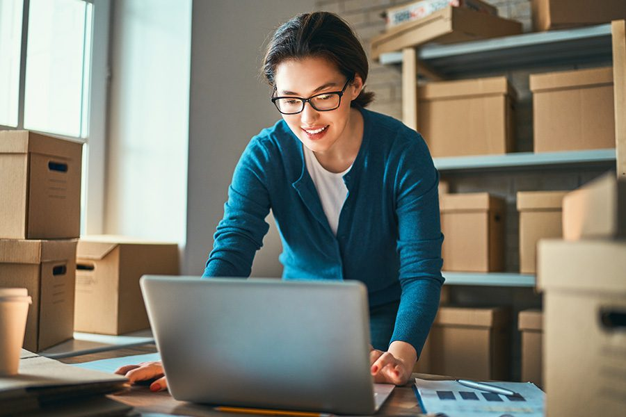 Business Insurance - Woman Business Owner is Standing at Her Desk Checking Online Orders on Her Laptop in a Warehouse Filled With Packages