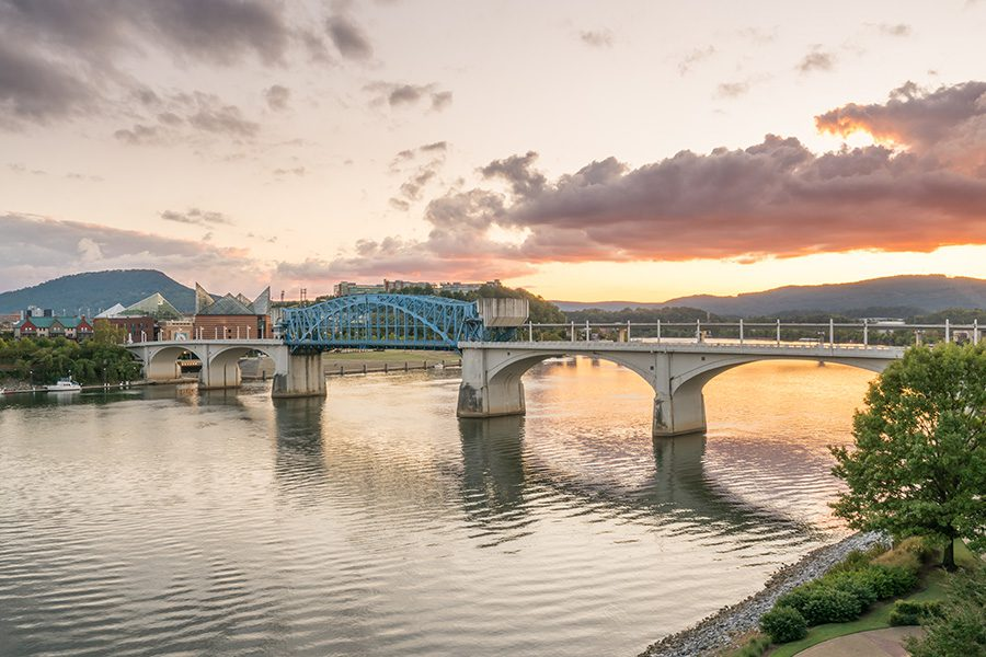 Chattanooga, TN - Long Distance View of Chattanooga, Tennessee City Skyline at Sunset Displaying a Large River and Bridge That Crosses it