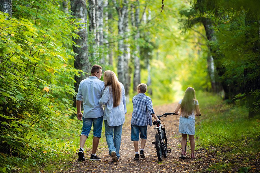 Employee Benefits - Rear View of a Family With Their Two Children Walking Down a Path in a Park While the Son Pushes His Bike