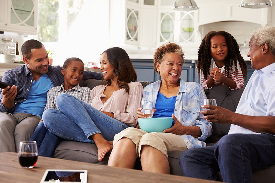 Personal Insurance - Happy Multi Generation Family Sitting Down at Home on the Sofa and Talking to Each Other