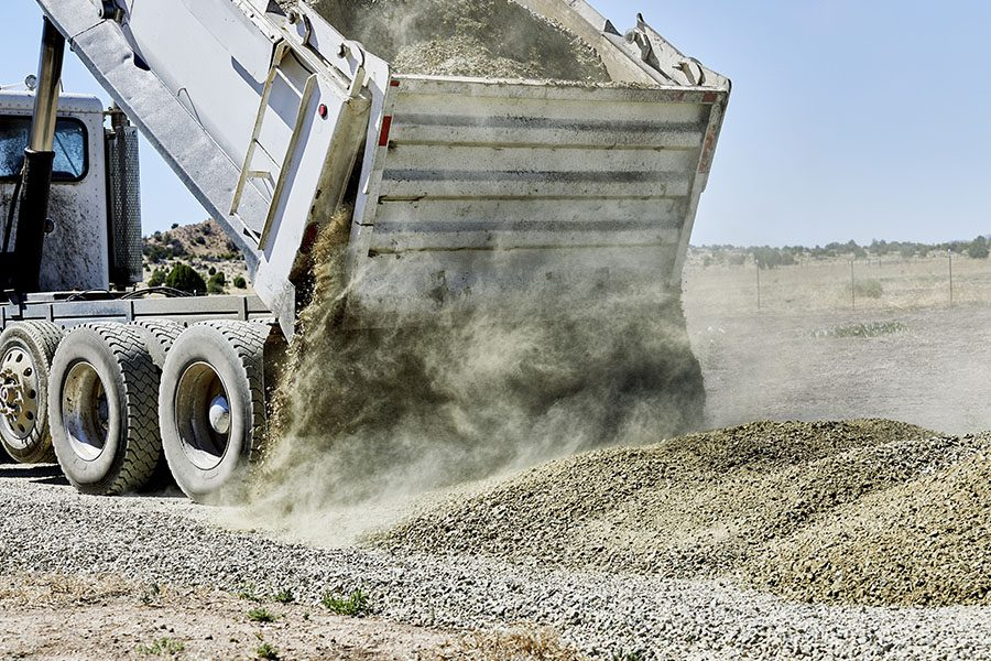 Sand and Gravel Hauler Insurance - Drump Truck Pouring Down Gravel to be Spread on a Driveway
