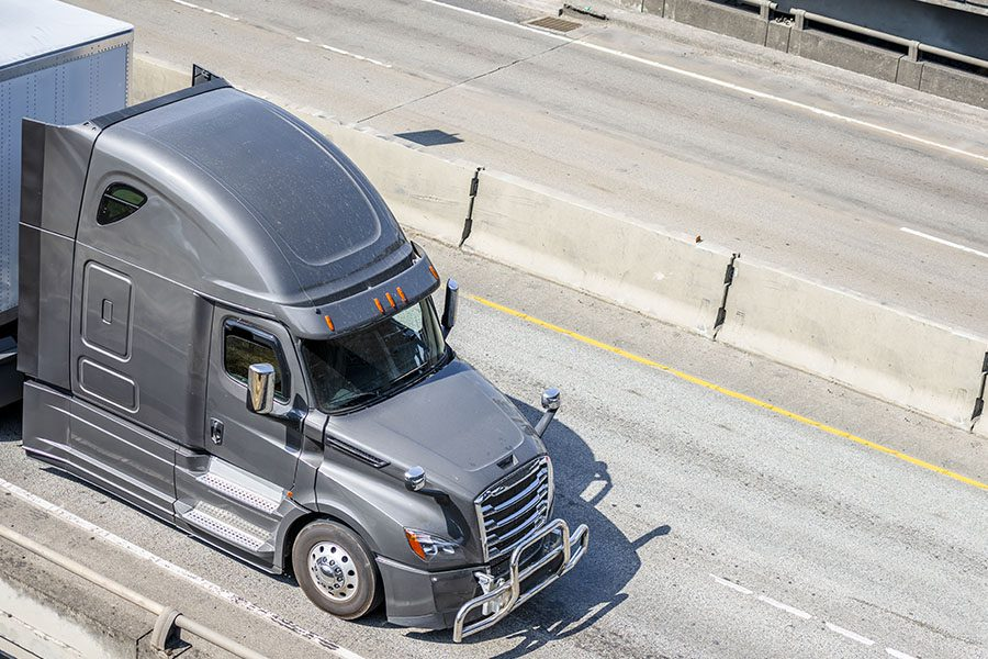 Transport and Delivery Insurance - Aerial View of a Gray Big Rig Long Haul Semi Truck Driving Down a Highway