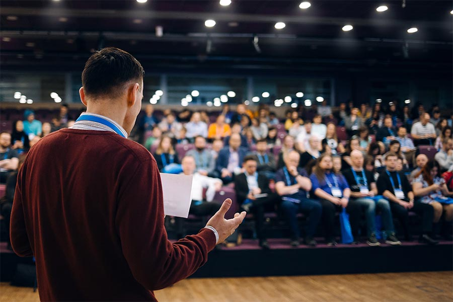 Event Insurance - Business Conference with a Man on Stage Talking About Performance