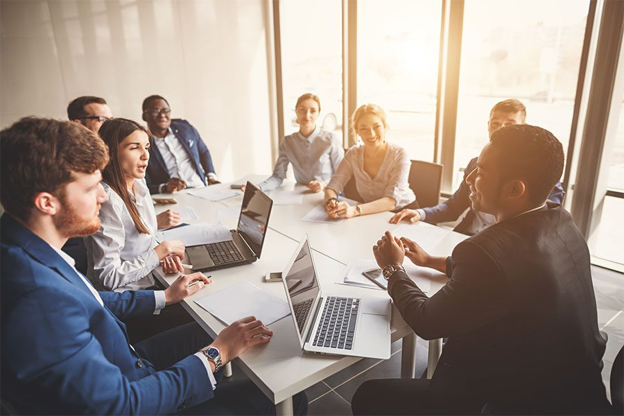 Business Insurance - View of a Group of Employees Sitting Around a Table During a Business Meeting in the Office with Sunlight Coming Through the Windows