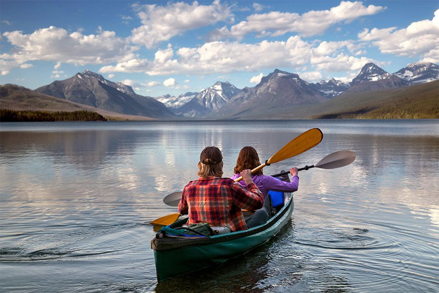 Client Center - Portrait of a Couple in a Canoe on a Scenic River with Views of Mountains in the Background