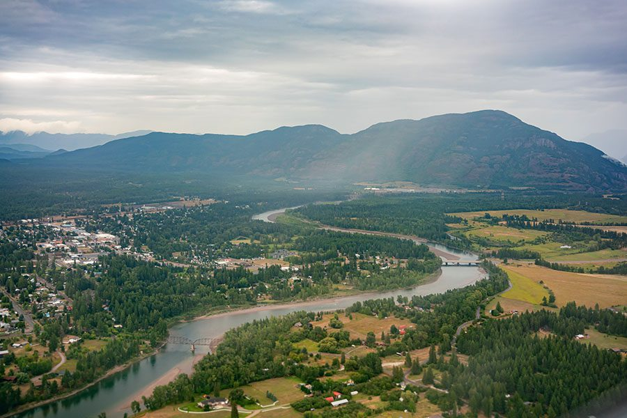 Kalispell MT - Aerial View of the City of Kalispell in Montana Surrounded by Green Foliage and Mountains