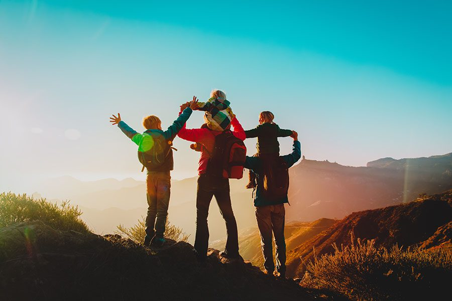 Personal Insurance - Rear View of a Cheerful Family with Three Kids Having Fun Hiking Through the Mountains at Sunset