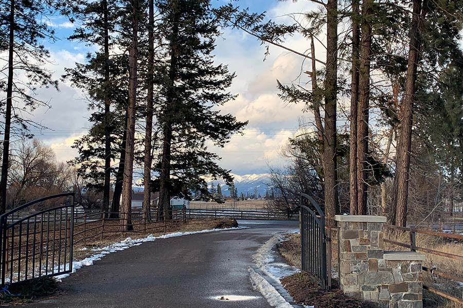Amazing Feedback - View of an Open Front Gate to a Horse Ranch in Montana During the Winter with Views of the Mountains in the Background