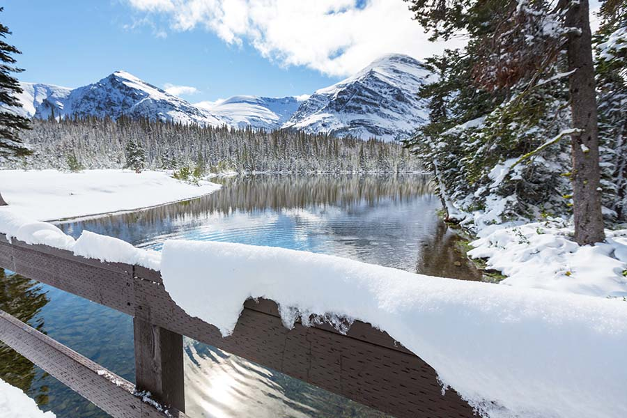 Compensation Disclosure - Scenic Winter Scene in a Park in Montana with Snow on the Mountains and Trees Next to a River