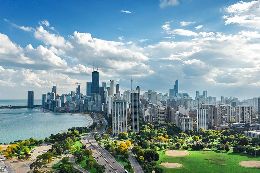 Contact - Aerial View of Downtown Chicago Illinois and the Neighboring River Against a Cloudy Blue Sky