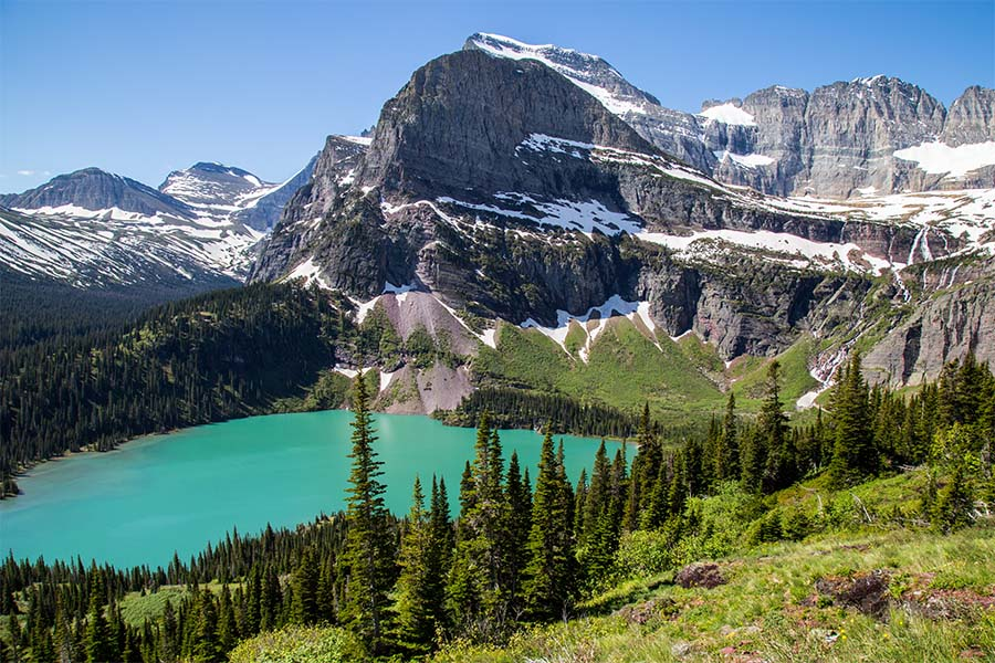 Contact - Scenic View of Glacier Park with a Lake Surrounded by Snowy Mountains and Green Trees in Montana