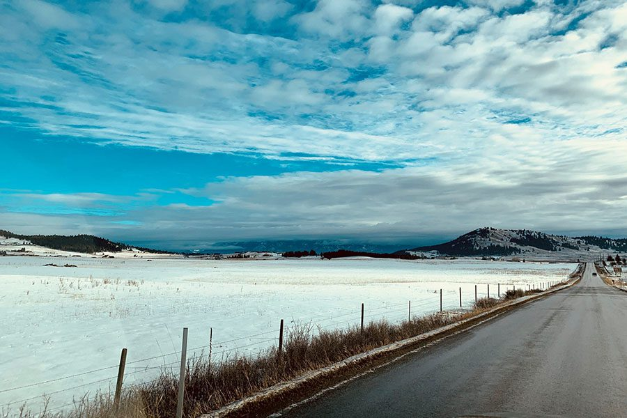 Join Our Team - View of an Empty Road Next to a Frozen Lake on a Cloudy Winter Day in Montana