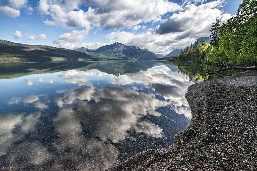 About Our Agency - View of the Shore Edge of Lake McDonald with Cloud Reflections in the Water and Views of Mountains in the Background