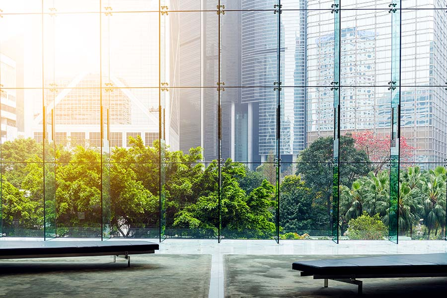 Bryan, OH - Glass Wall in a Modern Office Building Showing Reflection of Buildings and outside Courtyard with Trees