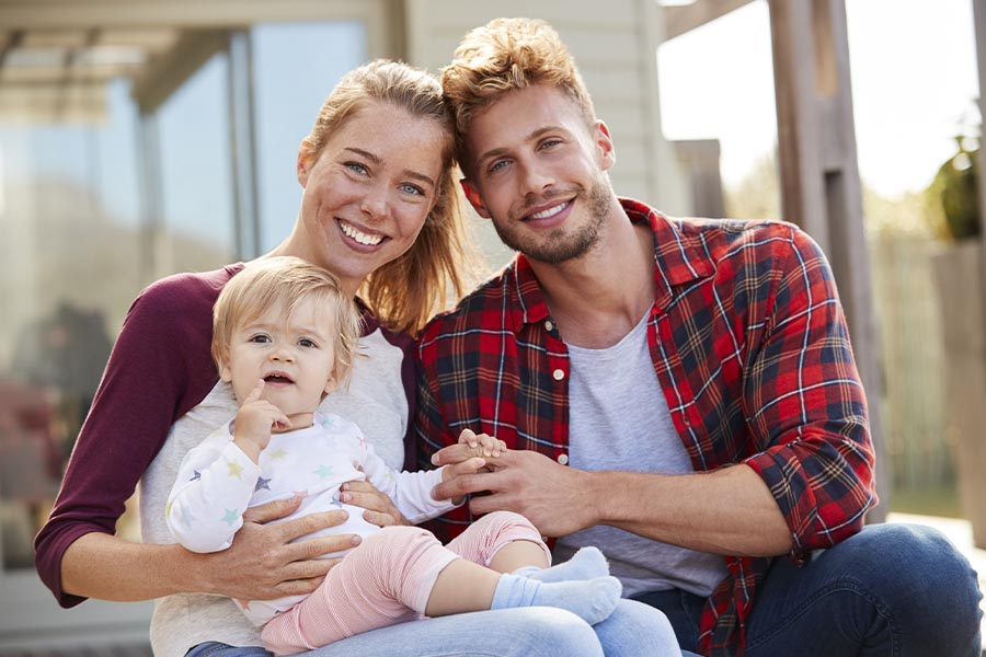 Personal Insurance - Portrait of a Young Family Smiling at Camera and Sitting on the Back Patio of New Home with Young Child on Her Mother's Lap